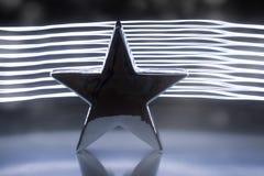 在黑暗的背景的一个大银色金属星与光线影响 免版税库存图片