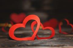在黑暗的背景的两红色纸心脏 亲人的一件礼物在情人节 免版税库存照片