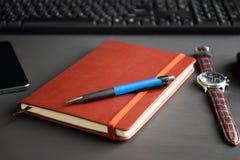 在黑暗的背景的布朗红色笔记本 免版税库存图片