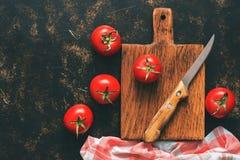 在黑暗的背景的新鲜的蕃茄,切板,方格的餐巾,刀子 顶视图,拷贝空间 被定调子的照片 免版税库存图片