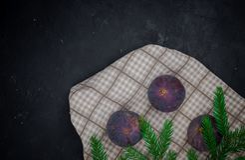 在黑暗的背景的无花果与一棵绿色圣诞树 在混凝土的米 免版税库存图片
