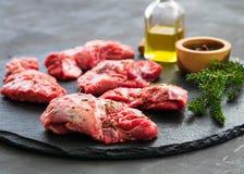 在黑暗的背景的未加工的猪肉面颊肉用迷迭香和香料 库存照片