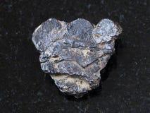 在黑暗的背景的未加工的钛铁矿石头 库存照片