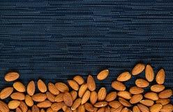 在黑暗的背景的杏仁堆 杏仁宏指令照片 与文本空间的有机食品土气横幅模板 免版税库存照片