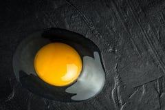 在黑暗的背景的残破的蛋黄 免版税库存图片