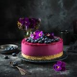 在黑暗的背景的没有被烘烤的蓝莓奶油甜点蛋糕 免版税库存照片