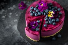 在黑暗的背景的没有被烘烤的蓝莓奶油甜点蛋糕 图库摄影