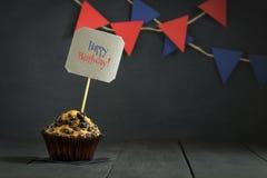 在黑暗的背景的生日杯形蛋糕 愉快的生日 明信片 祝贺 免版税库存图片