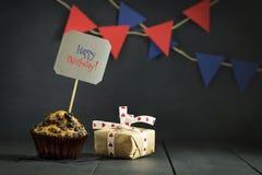 在黑暗的背景的生日杯形蛋糕 愉快的生日 明信片 祝贺 库存照片