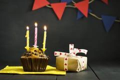 在黑暗的背景的生日杯形蛋糕 愉快的生日 明信片 祝贺 库存图片