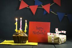 在黑暗的背景的生日杯形蛋糕 愉快的生日 明信片 祝贺 免版税库存照片