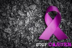 在黑暗的背景的紫色丝带了悟与中止巨蟹星座词 免版税库存照片