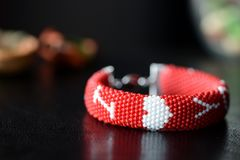 在黑暗的背景的红色成串珠状的我爱你镯子 库存图片