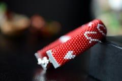 在黑暗的背景的红色成串珠状的我爱你镯子 免版税库存图片