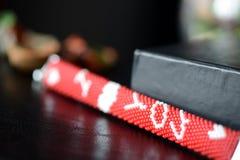 在黑暗的背景的红色成串珠状的我爱你镯子 免版税库存照片