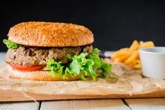 在黑暗的背景的经典汉堡 美国快餐 免版税库存照片