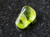 在黑暗的背景的翻滚的橄榄石宝石 库存图片