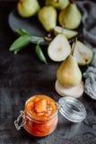 在黑暗的背景的自创梨果酱在背景新鲜的成熟梨 库存图片