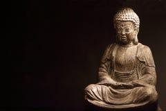 在黑暗的背景的菩萨雕象 库存图片