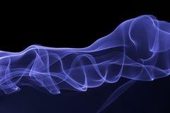 在黑暗的背景的蓝色烟 免版税图库摄影