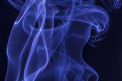 在黑暗的背景的蓝色烟 库存图片