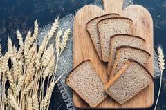 在黑暗的背景的被切的黑麦面包和麦子耳朵 平的位置 免版税库存照片