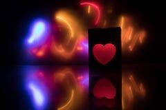 在黑暗的背景的被弄脏的霓虹心脏象 与红色明亮的五颜六色的心脏的拷贝空间在黑背景 库存图片