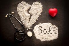 在黑暗的背景的被洒的盐与由盐做的伤心形状 库存照片