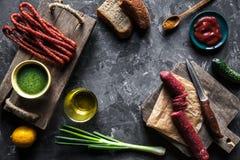 在黑暗的背景的香肠与烹调的元素 黄瓜,葱,番茄酱 图库摄影