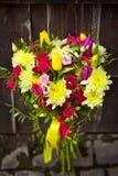 在黑暗的背景的黄色和桃红色婚姻的花束 库存图片
