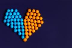 在黑暗的背景马赛克的心脏橙色蓝色 免版税库存图片