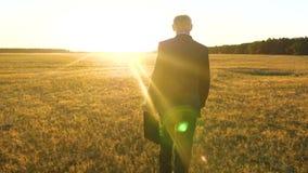 在黑暗的衣服的商人与黑公文包走通过在明亮的太阳的光芒的领域的一次重要会议的 股票视频