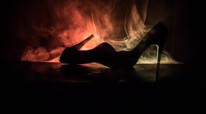 在黑暗的被定调子的有雾的背景的黑绒面革高跟鞋妇女鞋子 关闭 妇女供给动力或妇女控制权概念 库存照片