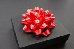 在黑暗的黑礼物盒对比了背景,装饰用一把红颜色弓,制造浪漫气氛 典型地使用为 库存图片