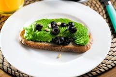 在黑暗的黑麦面包的鲕梨三明治从上面做用新鲜的切的鲕梨 库存图片