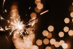 在黑暗的bokeh背景,新年快乐的燃烧的闪烁发光物 免版税库存图片