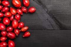 在黑木桌上的野玫瑰果 医药茶的成份 免版税库存图片