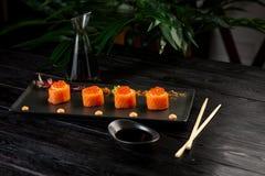 在黑木背景的一个黑色的盘子寿司卷与金枪鱼的集合 免版税库存照片