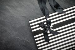 在黑条纹的白色包裹与把柄丝带和黑弓自由空间 库存图片