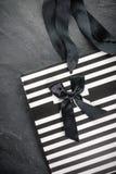 在黑条纹的白色小包与把柄丝带和一把黑弓 免版税库存图片