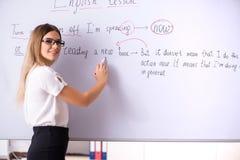 在黑板前面的年轻女性英语语言语文教员身分 图库摄影
