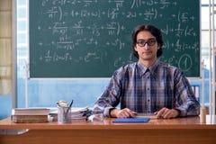在黑板前面的年轻滑稽的数学教师 免版税库存照片