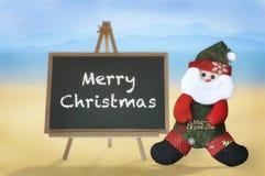 在黑板和圣诞老人的圣诞快乐词热带海滩背景的 免版税库存图片