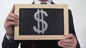 在黑板在商人手上,世界货币,财务的美元标志 股票录像