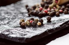在黑板岩的不同的胡椒香料 烹调的成份 概念吃健康 在黑暗的背景的各种各样的香料 愈合 免版税库存图片