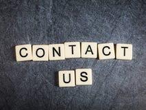 在黑板岩背景拼写的信件瓦片与我们联系 免版税库存照片