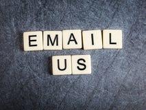 在黑板岩背景拼写的瓦片上写字给我们发电子邮件 库存图片