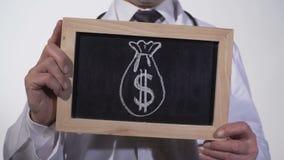 在黑板画的美元大袋在医生手上,昂贵的医学,贿赂 股票录像