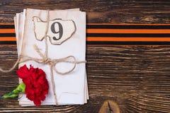 在黑板的乔治丝带在信件和一朵红色花下 免版税图库摄影