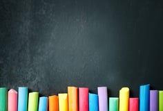 在黑板的五颜六色的蜡笔,画 回到背景学校 库存照片